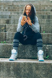 Sports woman and technology. Smiling Athlete with phone relaxing on stairs in the park after workout Stock Images