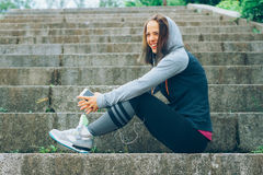Sports woman and technology. Smiling Athlete with phone relaxing on stairs in the park after workout Royalty Free Stock Image