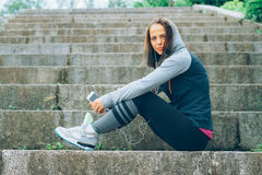 Sports woman and technology. Smiling Athlete with phone relaxing on stairs in the park after workout Stock Image