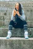Sports woman and technology. Smiling Athlete with phone relaxing on stairs in the park after workout Stock Photography