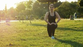 Sports woman training in park at sunset. Doing fitness, aerobics and stretching exercises, healthy and sporty lifestyle stock video footage