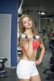 Sports woman trains biceps Stock Photos