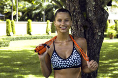 Sports woman in tropics poses smiling with skipping rope wearing stylish sportswear after training. Phuket island Stock Photography