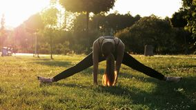 Sports woman try sits on a twine, doing fitness and stretching exercises, training in park at sunset, healthy and sporty stock video footage