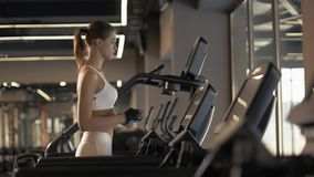 Sports woman using screen on treadmill for settings cardio exercise in gym club. Fitness woman walking on treadmill for cardio training in gym club. Sports woman stock footage