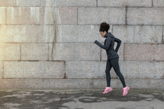 Sports woman warmed up on a city street. Before a workout Stock Photos