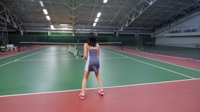 A sports woman who is engaged in tennis beats the ball through the net, the tennis player plays with the opponent who. A sportswoman who likes to play tennis on stock video
