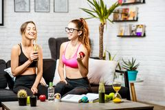 Sports women at home. Two young sports women talking on the couch during the break with healthy food after the training at home stock photography