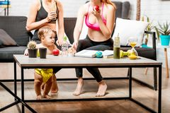 Sports women with baby boy at home. Sports women sitting on the couch after the training with baby boy playing near the table at home stock photography