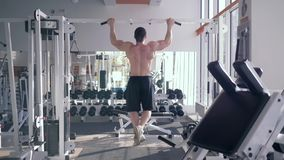 Sports workout, strong bodybuilder man with athletic body pulls up on bar during strength training at gym. View from back stock video footage