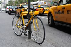 Yellow bike and yellow taxicabs Royalty Free Stock Images