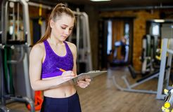 Sports young beautiful woman is an instructor in the gym. Young woman school sport coach. stock images