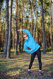 Sports young girl. Young woman in the blue jacket exercising on the forest Royalty Free Stock Images