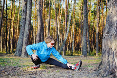 Sports young girl. Young woman in the blue jacket exercising on the forest Stock Photos