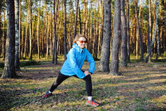 Sports young girl. Young woman in the blue jacket exercising on the forest Royalty Free Stock Image