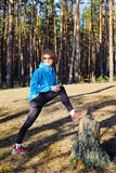 Sports young girl. Young woman in the blue jacket exercising on the forest Royalty Free Stock Photos
