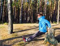 Sports young girl. Young woman in the blue jacket exercising on the forest Royalty Free Stock Photo