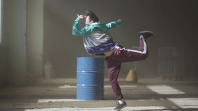 Sports young hip-hop dancer dancing near the barrel in an abandoned building in the fog. Hip hop culture. Rehearsal. Young rapper dancing in an abandoned stock video footage