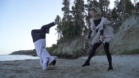 Sports young interracial couple dancing in free style outdoors. Asian guy and caucasian girl dancing contemporary dance stock footage