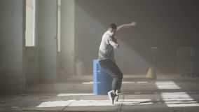 Sports young passionate hip-hop dancer performing. The man stretches his arms forward, then makes sharp movements to the. Portrait of young passionate hip-hop stock footage