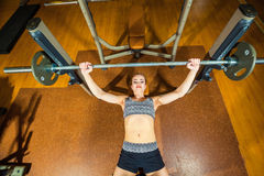 Sports young woman doing exercises with barbell on Stock Photography