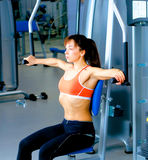 Sports young woman doing exercises on trainer back machine in the gym Stock Photo