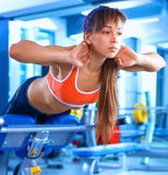 Sports young woman doing exercises on trainer back machine in the gym Stock Images