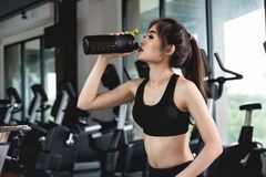 Sports young woman with protein cocktail in shaker sits in gym Stock Image