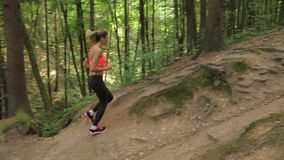 A Sports Young Woman Running Down the Hill Crest In The Wood By The Trail stock video