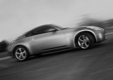 Sportscar. Sleek silver import sportscar with motion blurring Stock Photography