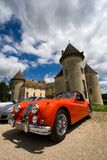 Sportscar and castle. BEAUNE, FRANCE - JUNE 12: Red classic Jaguar XK 140 sportscar in front of the Savigny castle. Savigny Castle Museum. June 12, 2010 in Royalty Free Stock Photo
