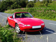 Sportscar in the country. Red Mazda MX5 sportscar on a country road Royalty Free Stock Photos