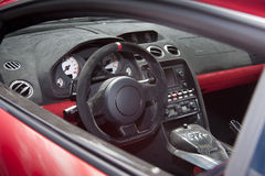 Sportscar dashboard and interior. Exotic sportscar interior in suede leather and carbon fiber Royalty Free Stock Photo