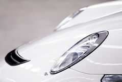 Sports car headlights. A white unmarked modern sports car headlights with grey background royalty free stock images