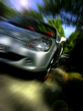 Sportscar speeding along. Toyota MR2 / MRS roadster sports car at speed from front in countryside on sun dappled road Royalty Free Stock Images