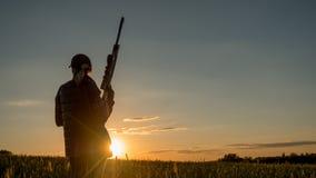Sportschießen und Jagd - Frau mit einem Gewehr bei Sonnenuntergang lizenzfreies stockfoto