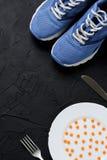 Sportschoenen en witte plaat met oranje pillen royalty-vrije stock afbeelding