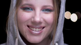 Sportsgirl en sudadera con capucha con el maquillaje colorido que aumenta sus ojos tímido y que ríe en cámara en fondo borroso de almacen de video