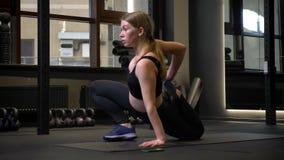 Sportsgirl joven y cansado que hace estirando ser concentrado y motivación en gimnasio metrajes