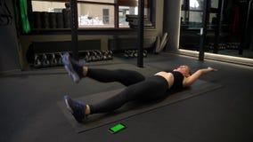 Sportsgirl joven y cansado que hace la subida cruzada de la pierna que es concentrada y motivada en gimnasio metrajes