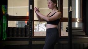 Sportsgirl motivado joven que hace las estocadas que son concentradas y serias en gimnasio metrajes