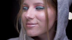 Sportsgirl rubio en sudadera con capucha con el maquillaje colorido que sonríe tímido en cámara en fondo borroso de las luces metrajes