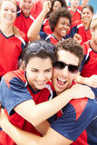 Sportåskådare i Team Colors Celebrating Arkivfoton