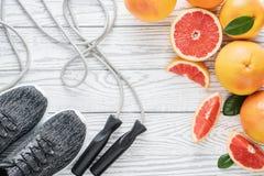 Sportskor, rep och nya grapefrukter, konditiontillbehör Begrepp av den sunda livsstilen, bantning, Arkivfoto