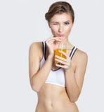 Sportsligt blinkar en härlig ung le flicka med ett exponeringsglas av orange fruktsaft i hans händer, den sunda uppehället, fotog Royaltyfria Bilder