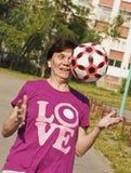 Sportsligt försöker en gammal kvinna entusiastiskt att fånga bollen som kastas till henne leka för fotboll Arkivfoton