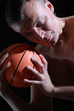 Sportsman. Studio shot of a handsome man with a basketball ball against the black background Stock Images