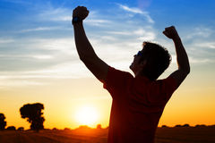 Sportsman with arms up celebrating success. Successful sportsman raising arms on golden sky back lighting sunset summer after cross running. Fitness male athlete Royalty Free Stock Photos