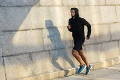 Sportsman. Athletic sportsman running at wall in city Stock Photography