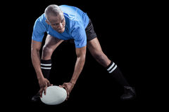 Sportsman bending and holding ball while playing rugby. On black background stock photo